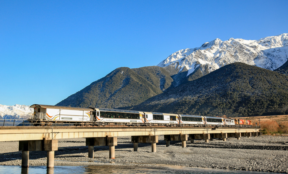 TranzAlpine crossing the Waimakariri River with snow on mountains